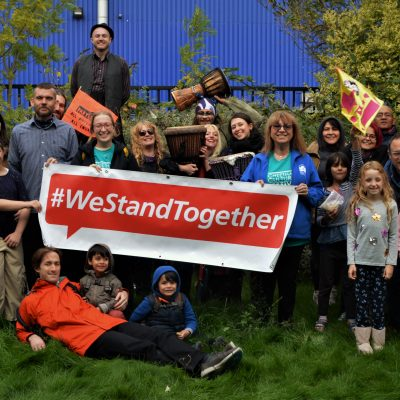"Group of adults and children standign in the Museum garden with a banner saying ""We Stand Together"""