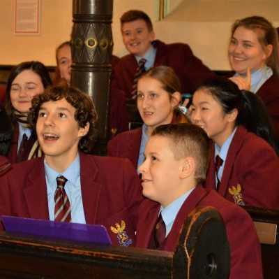 Learners in school uniform in the synagogue
